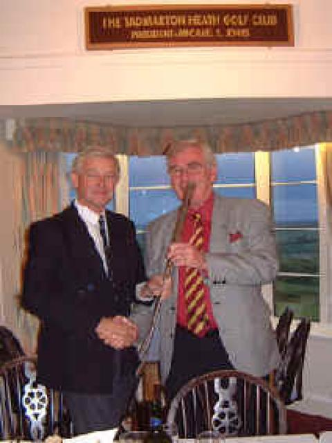 Photo shows Tony presenting the putter (or is he playing it!!) to the Midland's 2003 President  David Street